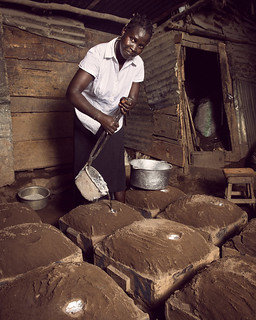 Betty pours molten metal into dirt-covered molds to make cooking pots | by World Bank Photo Collection