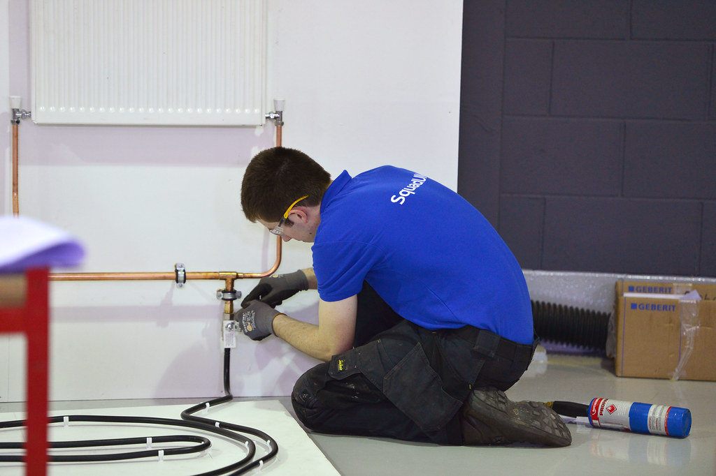 Plumber fixing radiator at FE World Skills Competition