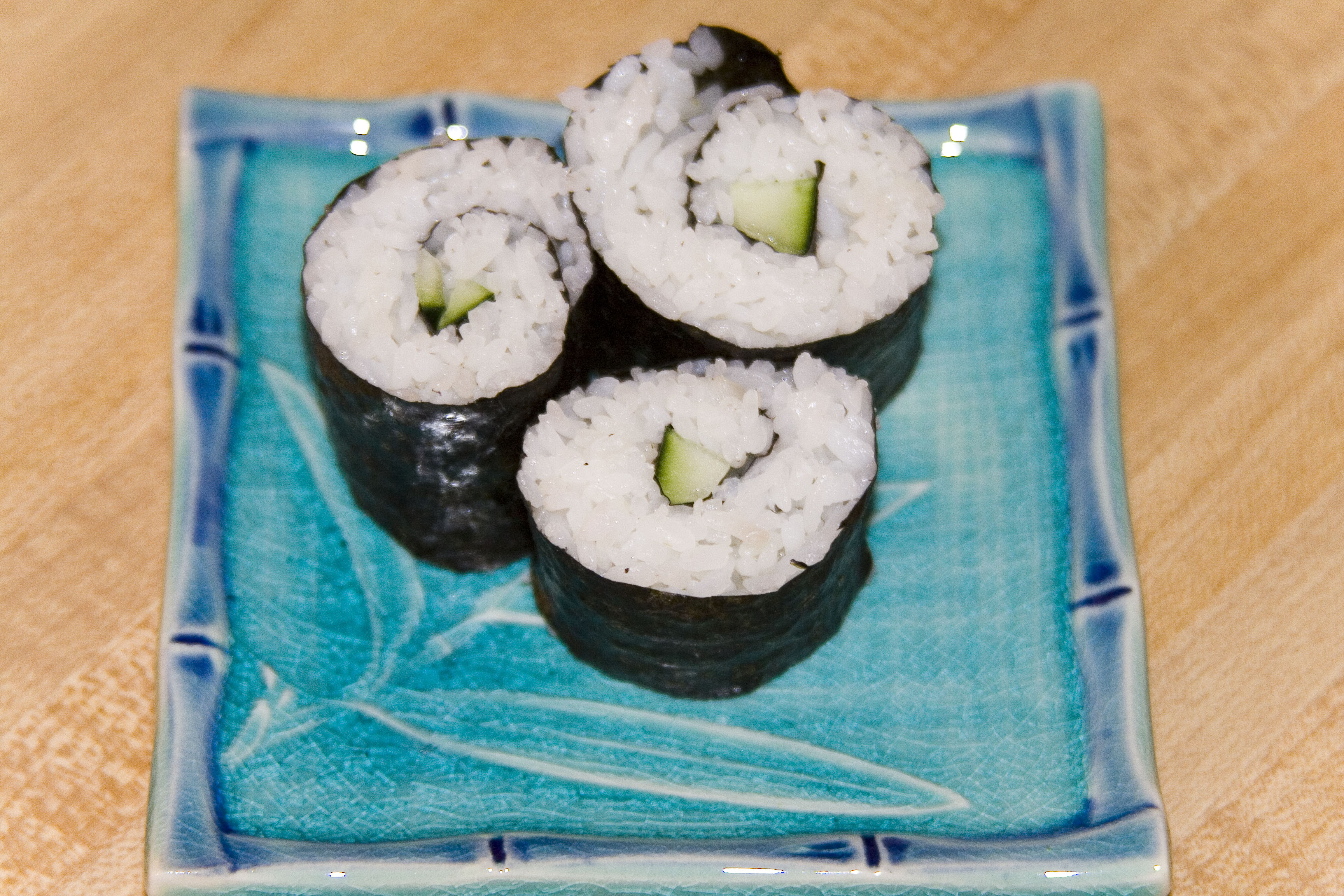 Cucumber rolls on a square turquoise plate