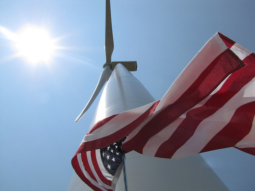 An American flag flying next to a new wind turbine