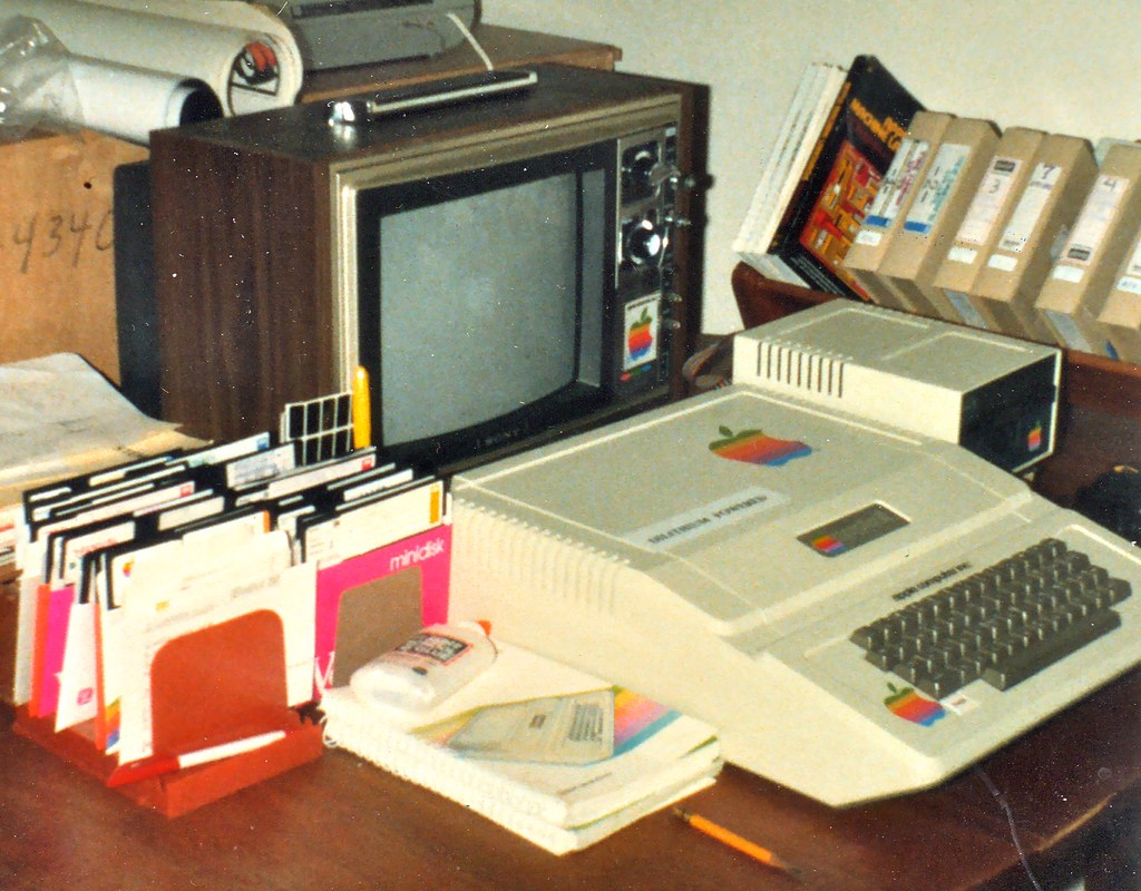 An old computer monitor and keyboard sitting on a cluttered desk