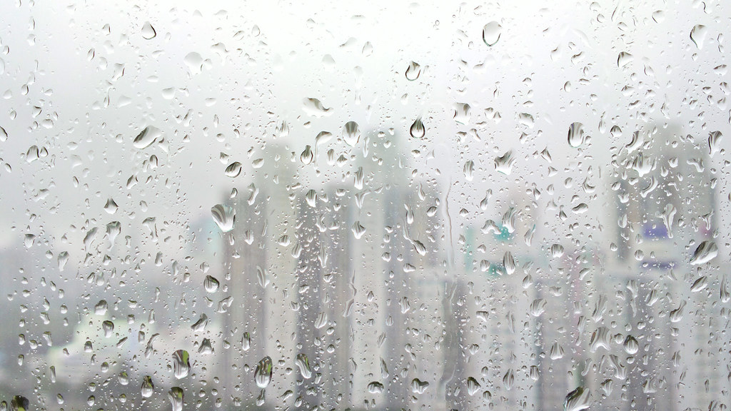 rain drops on glass with city background rain drops on
