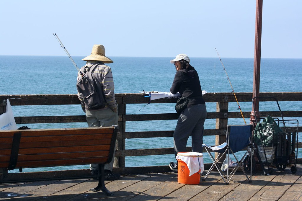Fish tales man and woman talking and fishing on the pier for Oceanside pier fishing reports