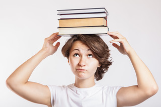 Schoolgirl with books on head | by CollegeDegrees360