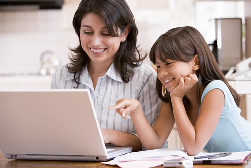 Woman and young girl in kitchen with laptop and paperwork smiling | by GSCSNJ