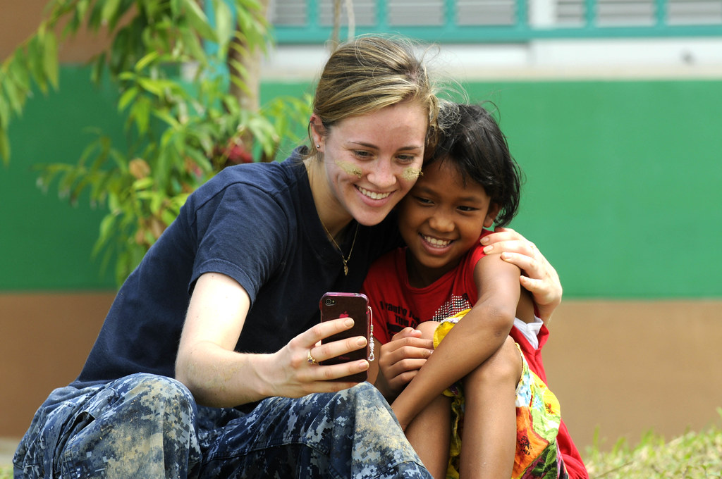A Sailor takes a photo with a Thai girl during a community