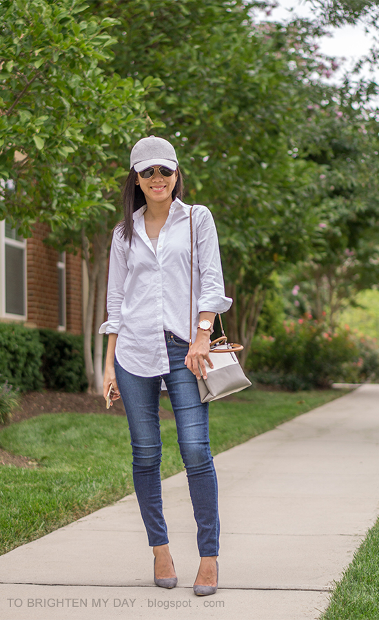 gray baseball cap, white dress shirt, colorblocked bag, skinny jeans, oversized watch, gray suede pumps