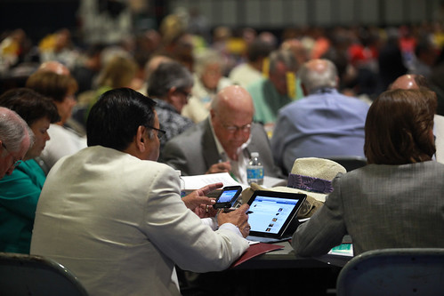 Multi-tasking during the May 4 plenary | by United Methodist News Service