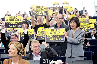 "MEPs from the Greens/EFA group hold up a sign saying ""Hello Democracy, Goodbye ACTA"" 