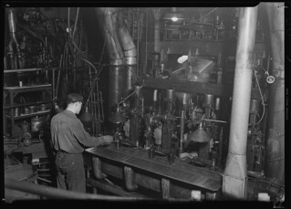 Second shot of a worker taking a bottle of of an I. S. automatic blowing machine for testing, March 1937 | by The U.S. National Archives