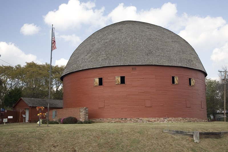 Still standing after over 100 years, the round barn's picturesque form compliments a blue sky filled with billowy white clouds.
