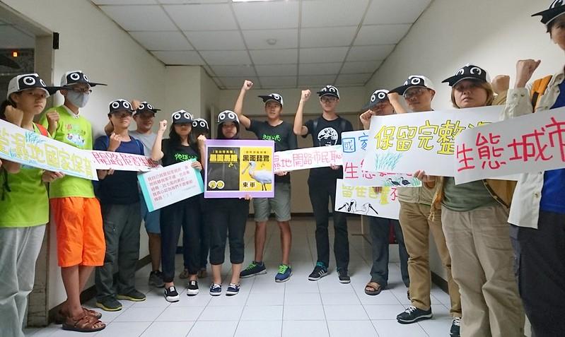 環保團體和在地青年於環評大會前舉標語,要求守護黑琵棲地,不要開馬路。攝影:李育琴