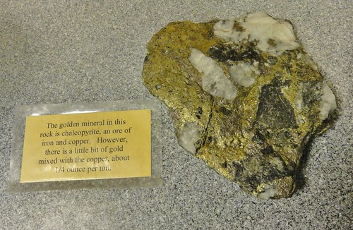 Image shows a golden rock with large pieces of quartz. Beside it is a laminated card that says,
