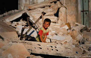 A child looking at what happened to his family house in Idlib after it was bombed by Assad warpalnes | by FreedomHouse