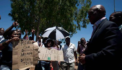 Republic of South Africa Human Settlements Minister Tokyo Sexwale speaking with residents of the informal area around Lenasia. Sexwale was seeking a solution to the crisis after demolition. | by Pan-African News Wire File Photos