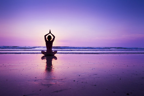 Woman practicing yoga on the beach | by egizu