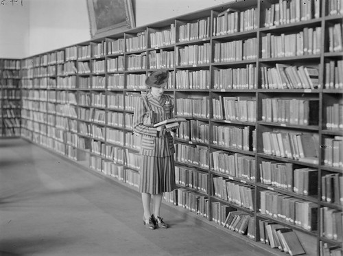 Young woman browsing shelves | by State Library Victoria Collections