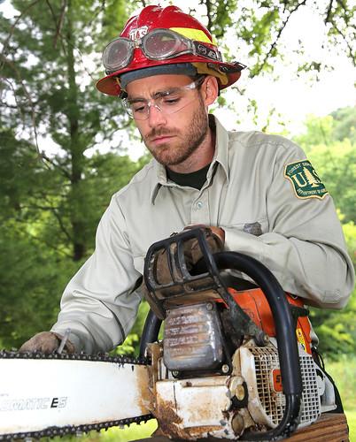 Matthew Martin sharpening his chainsaw