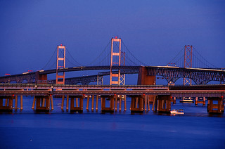 Both lower and high tier views of the Bay Bridge at sunset.