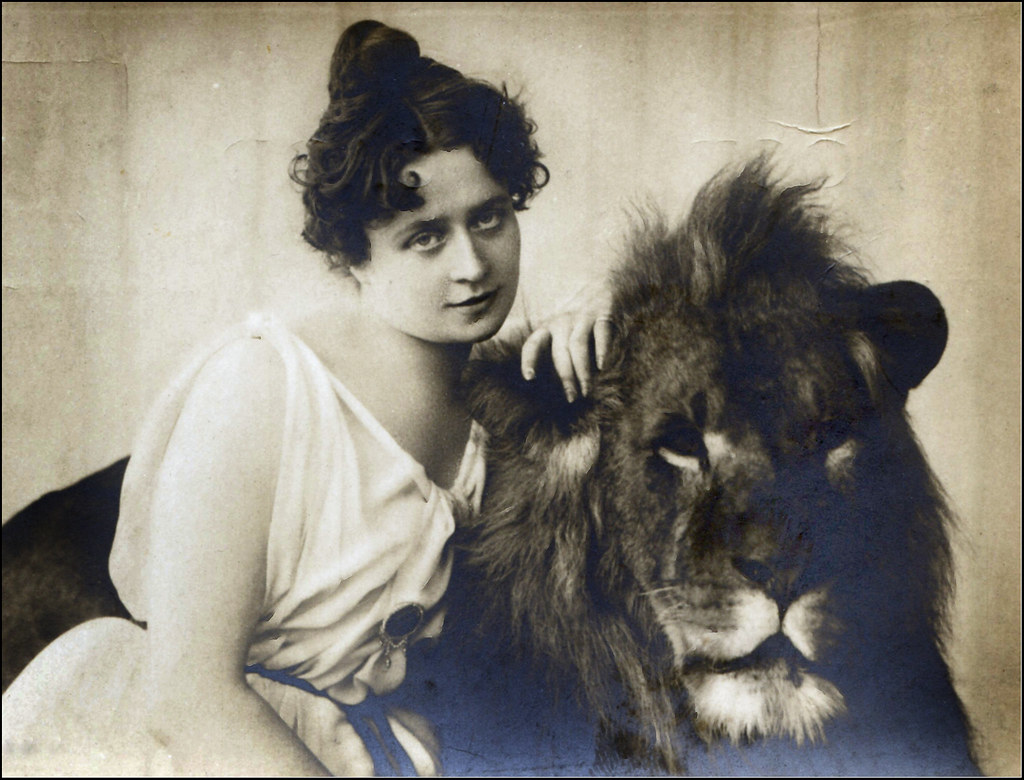 Lion tamer Claire Heliot poses with her arm draped over a lion's mane