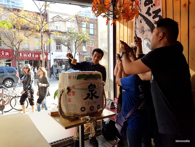 foodies taking photos of sake barrel
