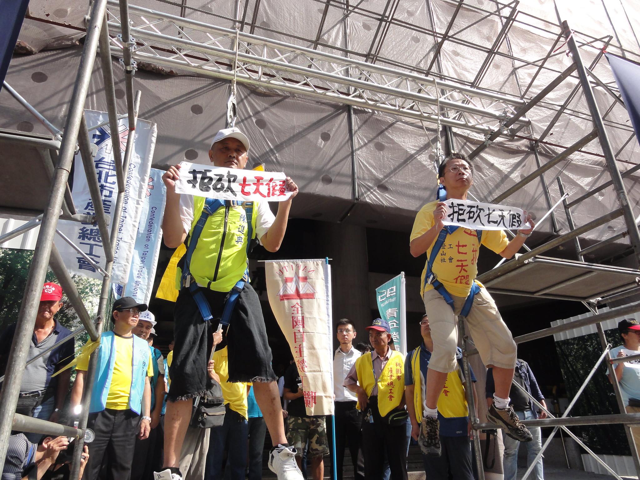勞團用懸掛上吊的方式,表現工人的休假權「命懸一線」。(攝影:張智琦)