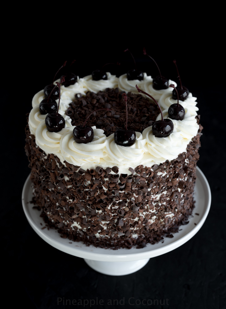 layer cake covered in chocolate curls on a white cake stand, decorated with whipped cream and dark cherries