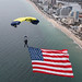 A SEAL on the U.S. Navy parachute demonstration team, the Leap Frogs, flys an 800-square-foot American flag during a rehearsal for the Lauderdale Air Show.