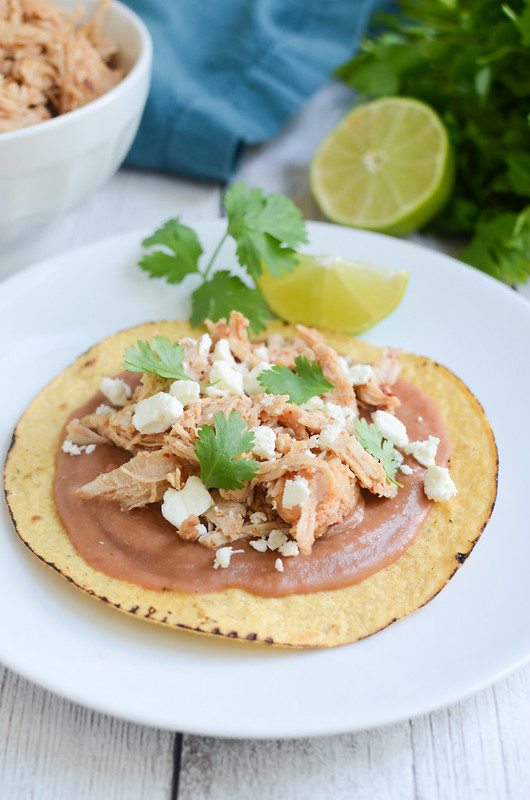 Crockpot Sweet and Spicy Tostadas - the most delicious turkey cooked in the crockpot with a chipotle pineapple sauce! Put it on tostadas with refried beans, cheese, and fresh cilantro!