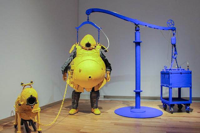 《イエロー・スーツ》 放射能防護服の機能を持つ初期作品。自分とペットのための防護服になっている。ガイガー・カウンターがすでに搭載されており、鉄板と鉛でできているため放射線に対する遮蔽性は高い。ただし、重すぎて動けないため、《アトムスーツ》に至る過程で徐々に機能性が上がっていく。