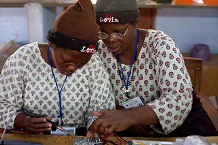 Women work together on solar lighting circuit boards | by UN Women Gallery
