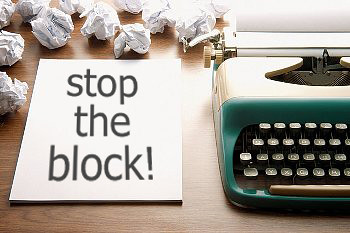 "A piece of paper sits next to a typewriter. On the paper are the words, ""Stop the block!"""