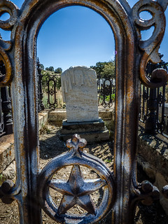 Tombstone viewed through the ornate iron grave fence. | by Chris (Midland05)