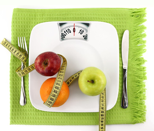 Diet concept. Fruits with measuring tape  on a plate like weight scale | by BahrainPersonalTraining