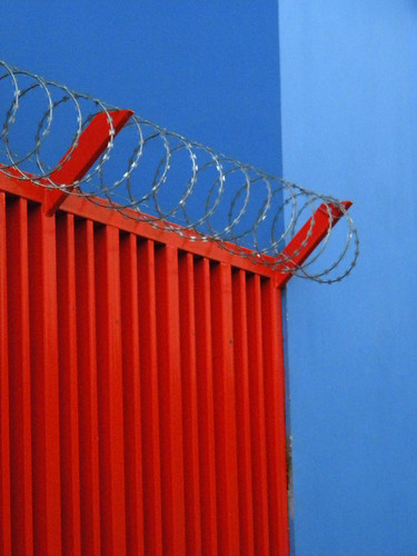 razor wire on a red wall