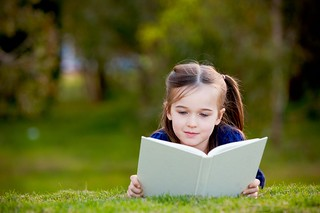 Five year old girl reading outdoors