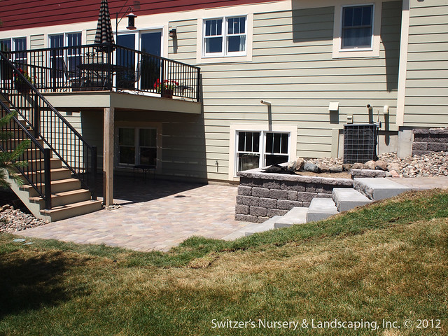 paver patio under deck with retaining wall steps