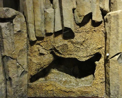 Image shows a replica of the Columbia River Basalts, complete with columnar jointing. In the center is a hole that's roughly shaped like an animal on its back with its feet in the air.