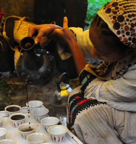 woman pouring coffee in cups