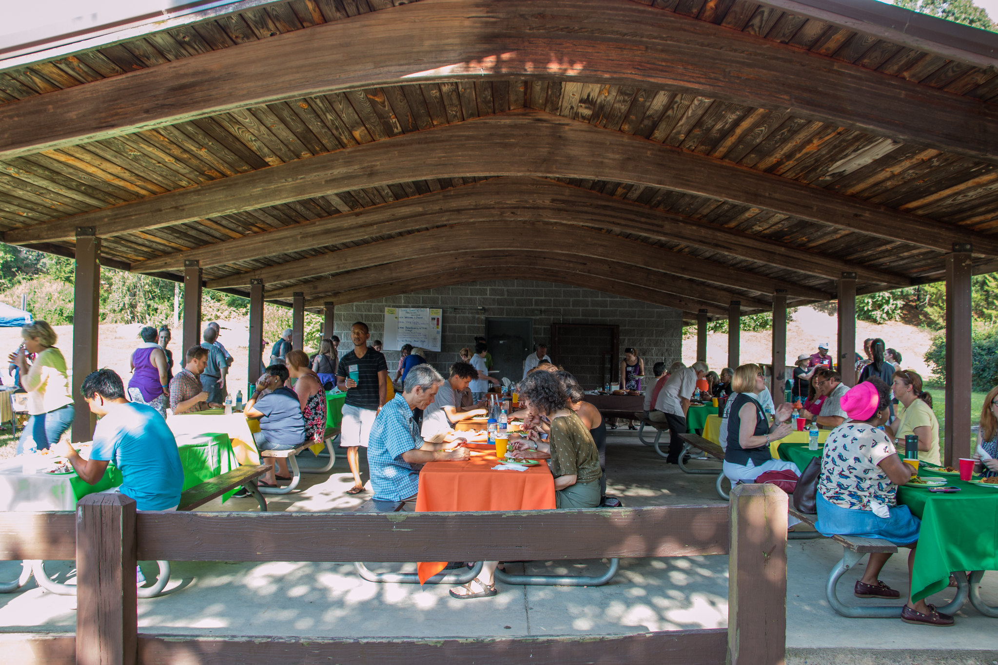 A photo of the Nellie's Cave Park picnic shelter. A large crowd of people sit inside the shelter at various picnic tables covered with bright tablecloths.