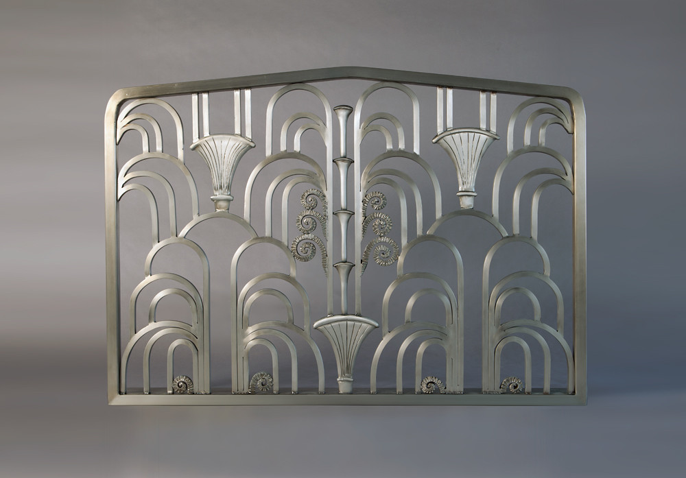 This highly complex beauty is based upon two constraints- 	One being the shape or opening of the clients hand carved Limestone Fireplace Surround- 	and the 2nd  	being the love and affection for the work of Art Deco Metal maestro- 	Edgar Brandt.  	Edgar Brandt was considered by many to be the PREMIER metalsmith 	of the Art Deco Era.  	Currently