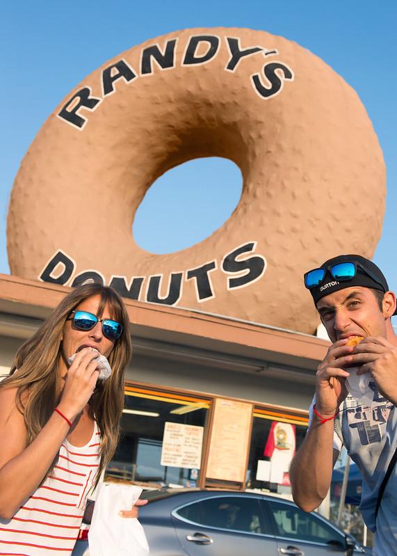 Comer una rosquilla frente al donut gigante de la tienda Randys Donut