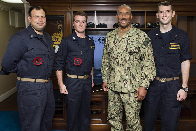 From left to right, Lt. Joshua Mills, Lt. Teddy George, Commander, Carrier Strike Group (CSG) 10 Rear Adm. Jesse Wilson and Lt.