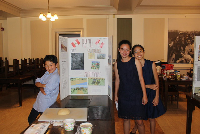 Three students beam with pride over their collaborative group architecture project