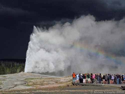 A rainbow appears in the mist of Old Faithful Geyser, Yellowstone National Park, Wyoming