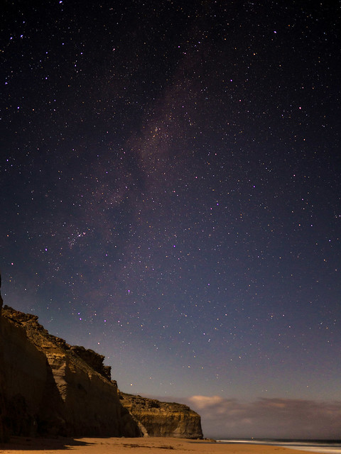 A starry night sky over a beach and cliff tops.