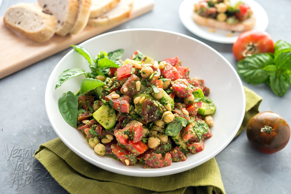 Oil-free Pesto Tomato Chickpea Salad in a white bowl on a steel background