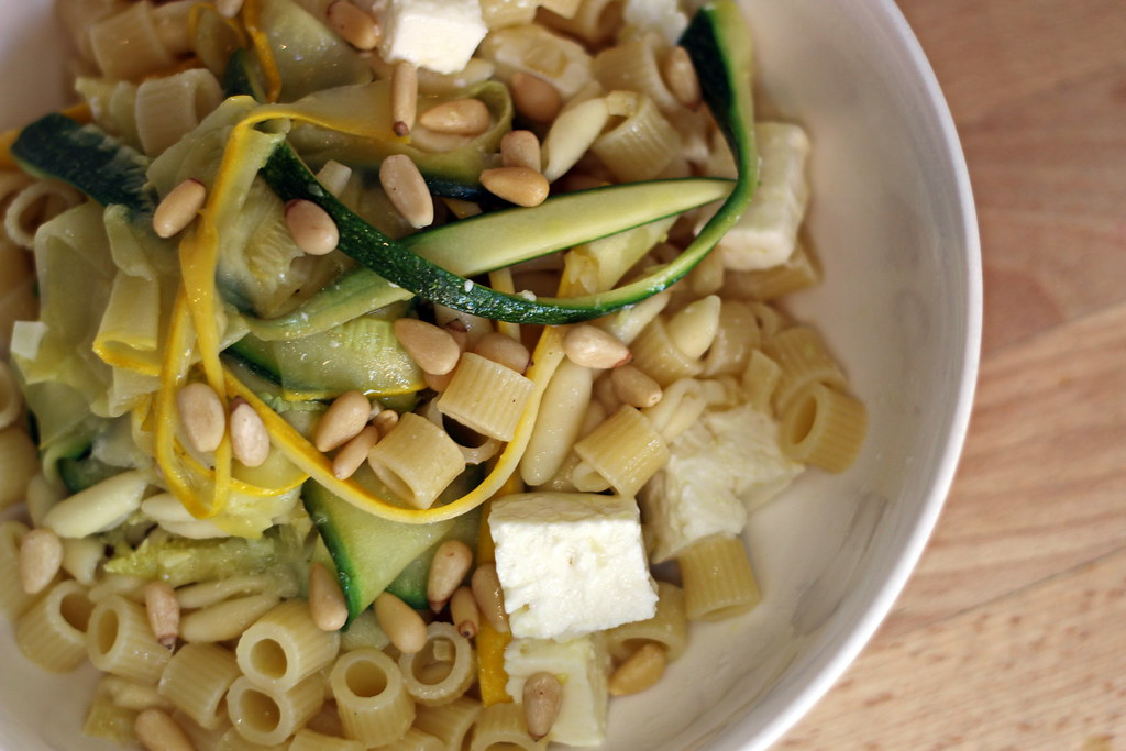 Pasta with courgette, feta and pine nuts in bowl