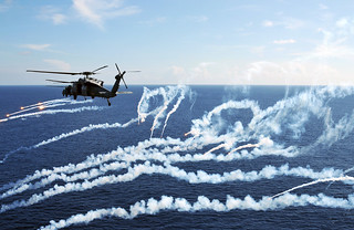 A helicopter fire flares. | by Official U.S. Navy Imagery