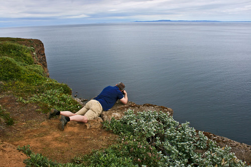 On the edge of a cliff.  Símon photograping birds. | by Inga Arna